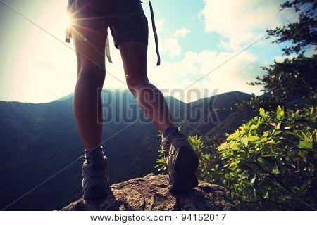 young woman hiker legs on sunrise mountain peak rock
