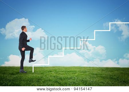 Businessman walking with his leg up against blue sky over green field