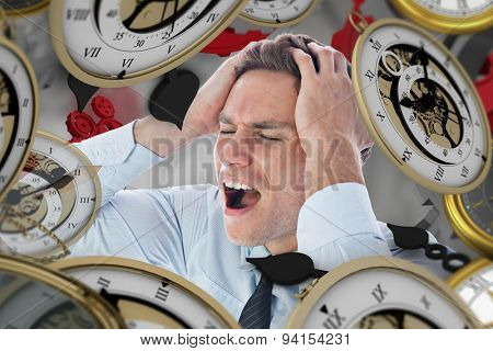 Stressed businessman with hands on head against grey vignette