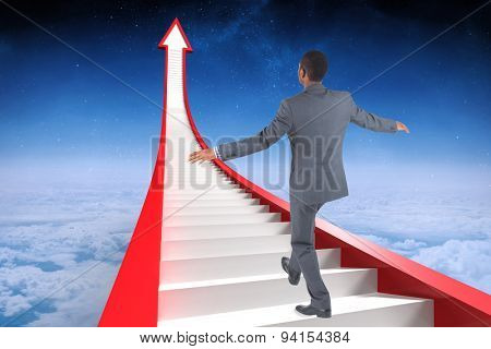 Businessman performing a balancing act against white clouds under blue sky