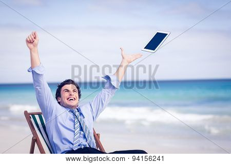 Carefree businessman throwing up his tablet in the air on the beach