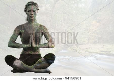 Calm blonde sitting in lotus pose with hands together against rapids flowing along lush forest