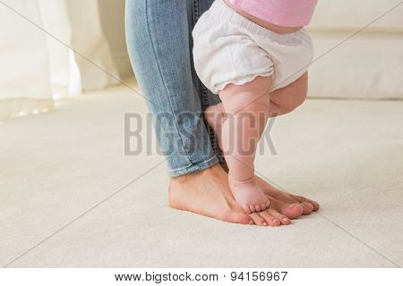 Happy mother with her baby girl learn to walk at home in the living room