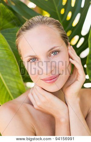 Beautiful blonde smiling at camera behind leaf at the health spa