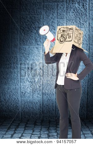 Anonymous businesswoman holding a megaphone against dark grey room