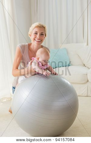 Happy mother with her baby girl the exercice ball at home in the living room