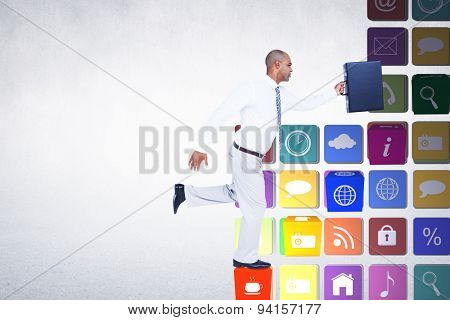 Businessman running with briefcase against grey room