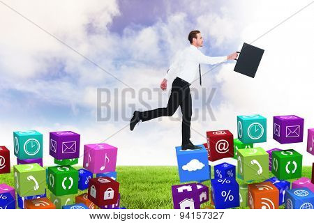 Businessman walking with his briefcase against blue sky over green field