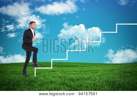 Businessman walking with his leg up against green field under blue sky
