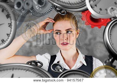 Thinking redhead businesswoman against grey background
