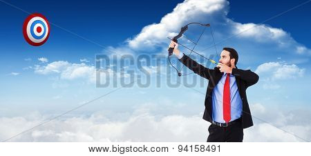 Focused businessman shooting a bow and arrow against bright blue sky with clouds