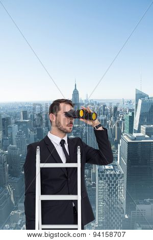 Businessman looking on a ladder against new york city
