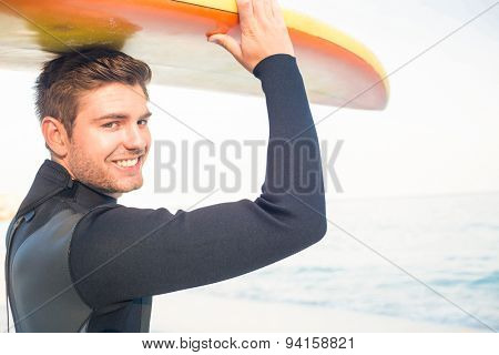 Man in wetsuit with a surfboard on a sunny day looking at camera