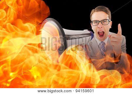 Geeky businessman shouting through megaphone against black