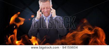 Businessman with headache against dark grey room