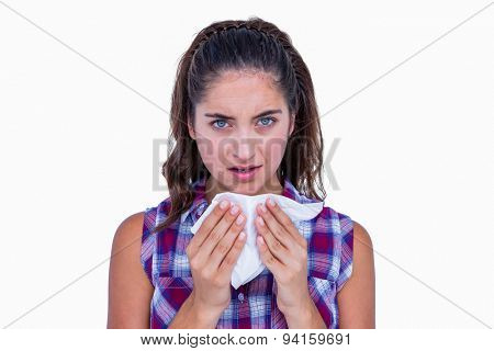 Pretty brunette woman blowing her nose on white background