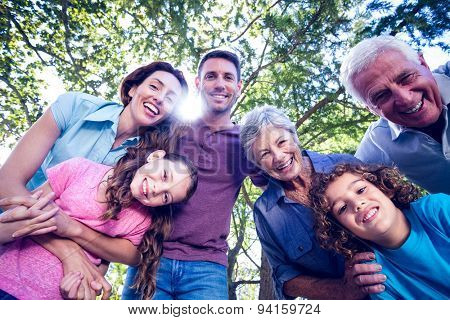 Happy family smiling at the camera on a sunny day