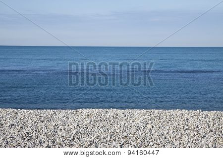 Calm Sea With White Stones On The Beach