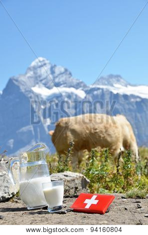Swiss chocolate and jug of milk on the Alpine meadow. Switzerland
