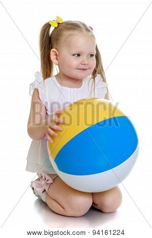 Beautiful little girl on her knees with the ball in his hands