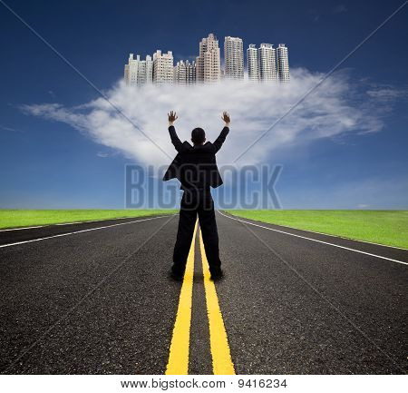 businessman standing on the empty road and watching the future city