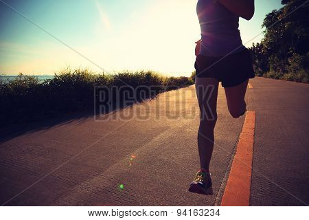 young fitness woman running on sunrise seaside trail,vintage effect