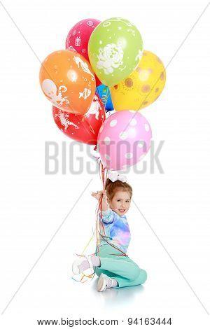 Girl in kindergarten is holding a bunch of balloons