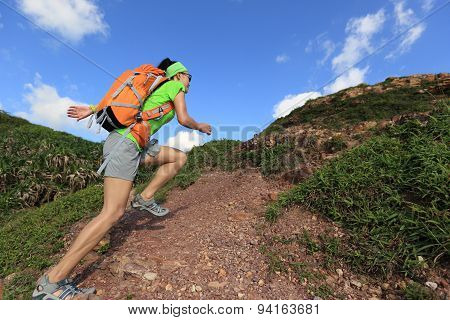 young woman backpacker running on mountain trail