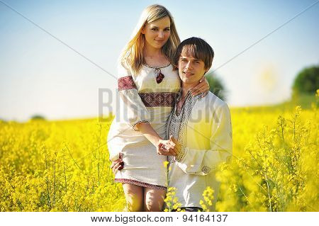 Couple On Traditional Dress At Yellow Flowers Field