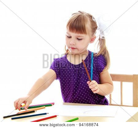 Cute little girl drawing with markers at the table