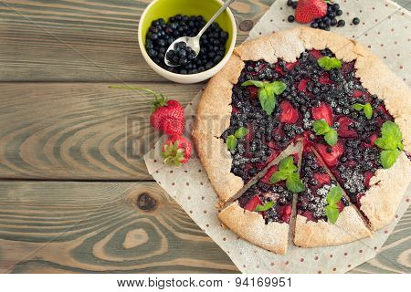 Homemade sea biscuit with strawberries and blueberries on wooden background. Summer still life.