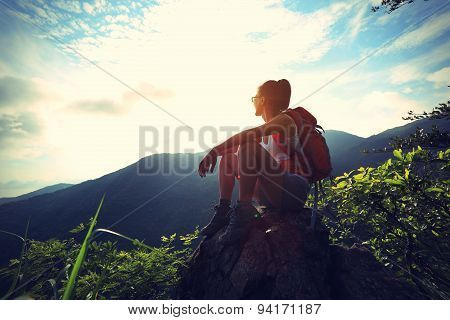young woman backpacker enjoy the view at seaside mountain peak