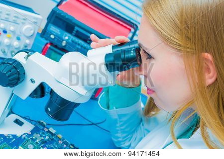 Blonde  young computer technician testing a printed circuit board with a microscope