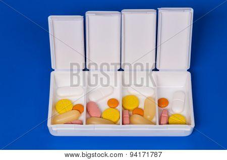 Dispenser with medicine pills on a blue background