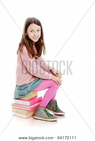 Portrait of beautiful girls 7-8 years old that sits on the books