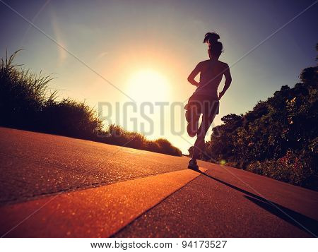 young fitness woman legs running on sunrise seaside trail,vintage effect