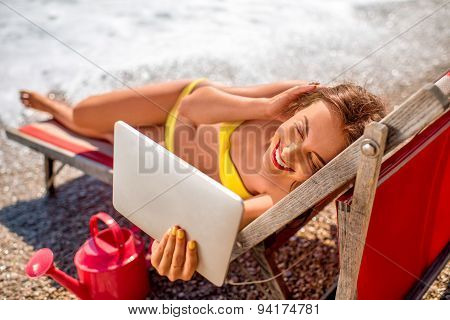 Woman making selfie with digital tablet on the beach