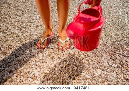 Woman's legs with watering can on the beach