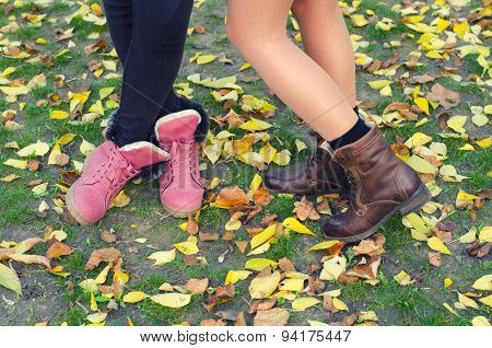 Legs And Shoes Of Young Girls Standing On The Dry Leaves And Grass On Beautiful Autumn Day