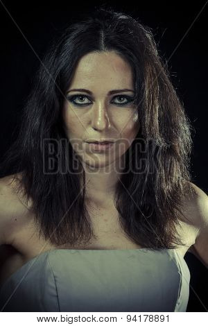 sad brunette woman with long hair and evening gown