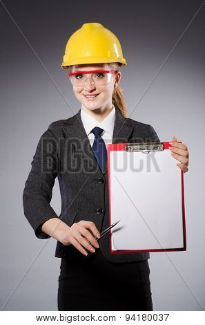Female engineer with helmet and paper isolated on gray
