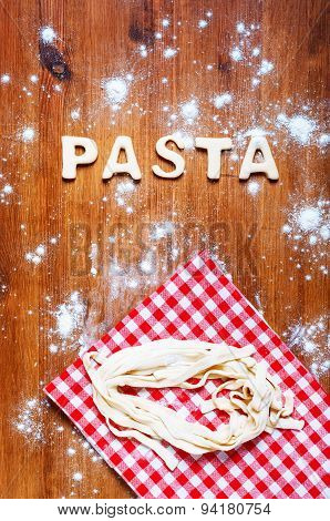 Letters of dough and pasta on the wooden table. Kitchen background
