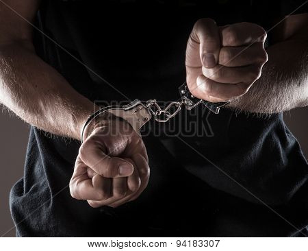 Man handcuffed hands, close-up.