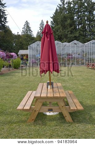 Picnic Table With A Red Umbrella.