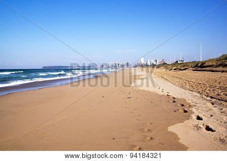 Footprints In Sand Along Durban Beach With City Skyline