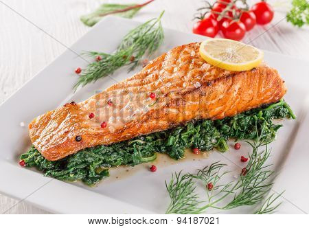 Salmon steak on white plate, close-up