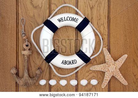 Decorative lifebuoy, wooden anchor, starfish and cockle shells over old oak background.