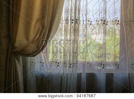 Gathered Curtains And Blinds On The Window Of The Room