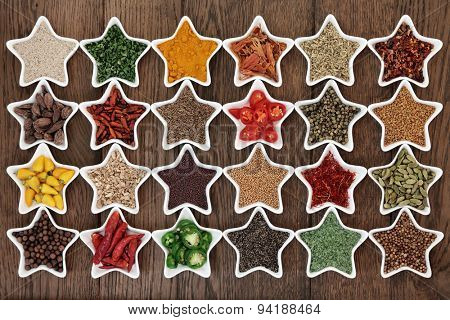 Large herb and spice selection in star shaped porcelain dishes over old oak background.