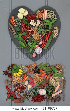 Herb and spice ingredients on heart shaped slate and loose over grey wooden background.